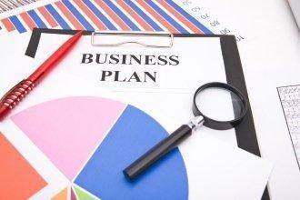 Бизнес план и лупа лежат на столе