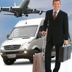 Изображение мужчины с чемоданом, который стоит возле машины в аэропорту