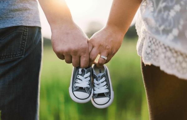 Мужчина и женщина держут детские кеды