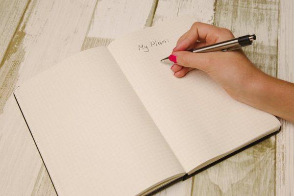 Тетрать, надпись на английском мой план, женская рука держит ручку