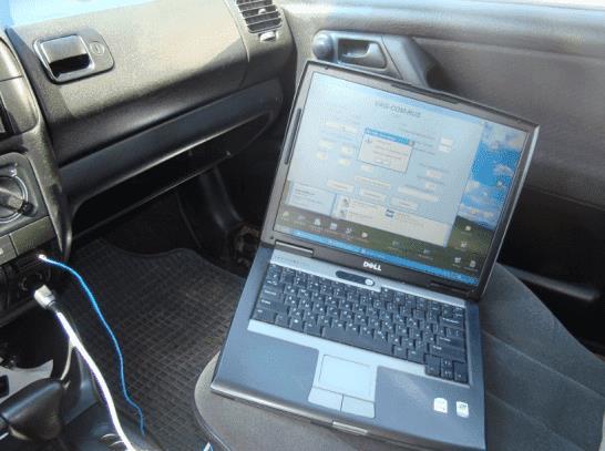 На фото: Диагностика авто при помощи адаптера и ноутбука