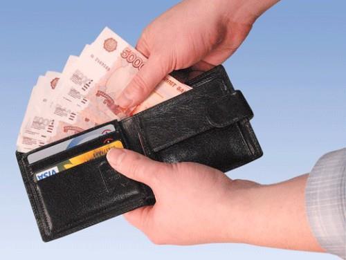 Мужчина достаёт из бумажника пятитысячные купюры