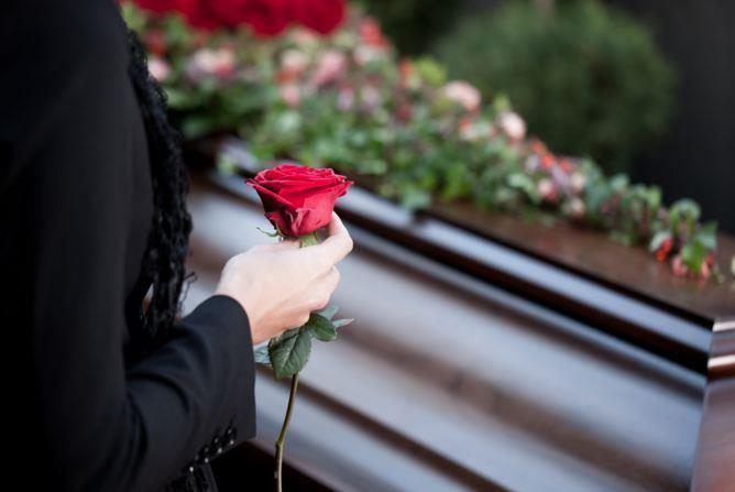 Девушка подносит цветы на погребении