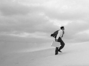 Рисунок мужчины, который с чемоданом идет по пустыне