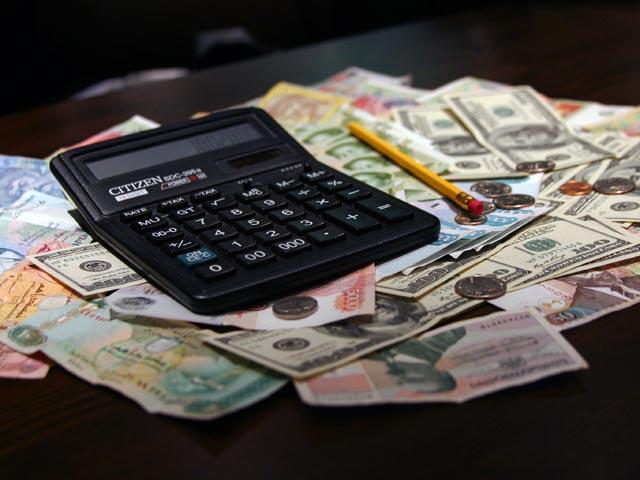 Купюры разных стран, калькулятор и карандаш лежат на столе