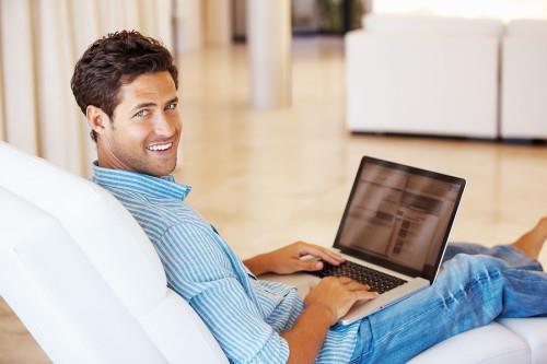Мужчина сидит на диване с ноутбуком в руках и ищет идею для бизнеса в интернете