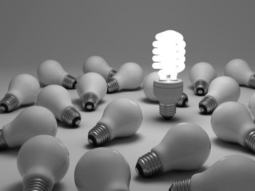 Горящая люминесцентная лампочка по среди других обычных